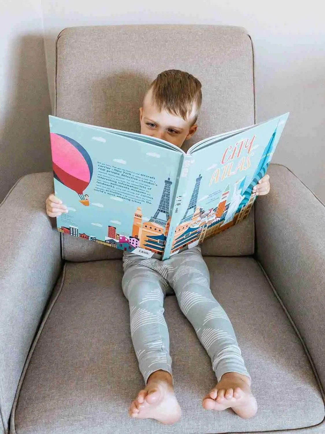 Little boy sitting in chair reading a kids city atlas of places to visit on future family trips
