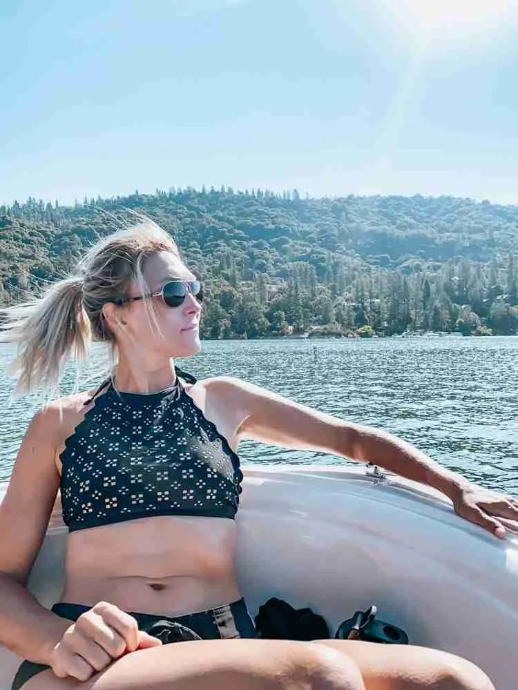 Mom on front of boat under shining sun on Bass Lake California