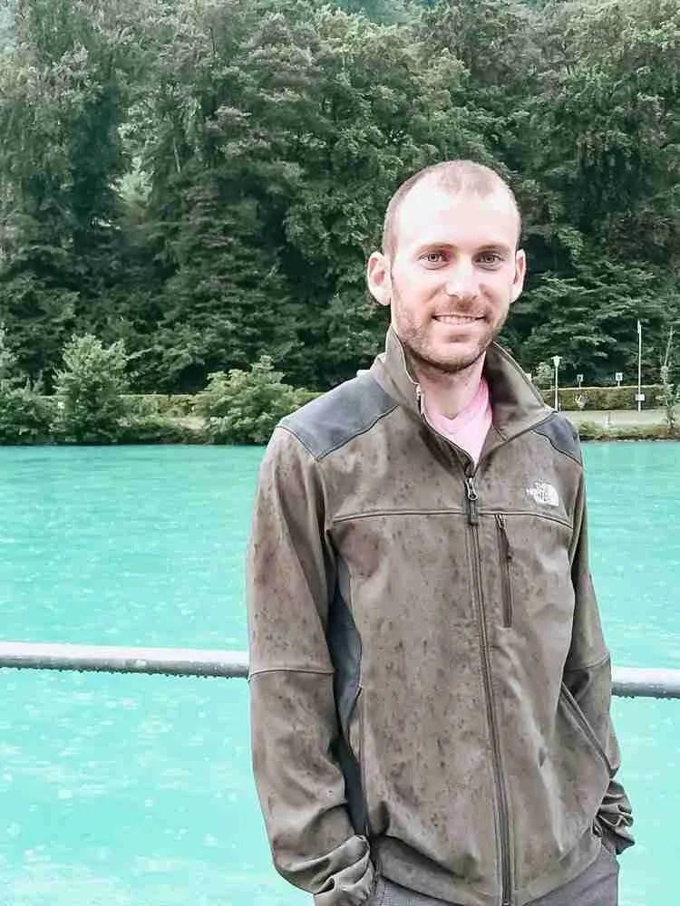 Man smiling in front of teal water at Interlaken