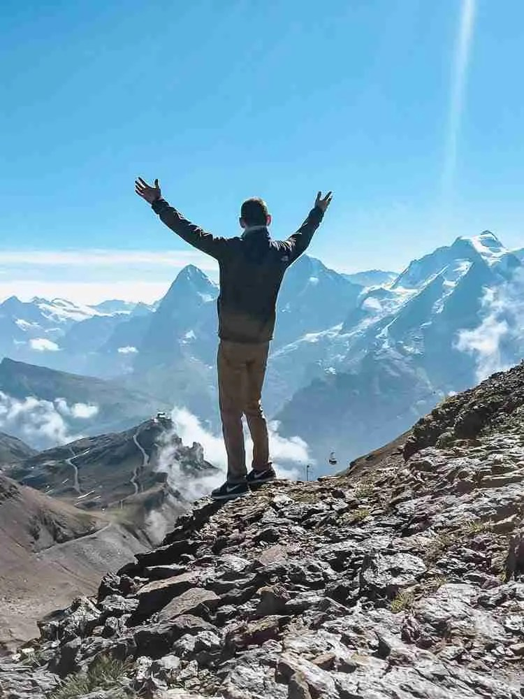 Man standing on edge of mountain in Swiss Alps