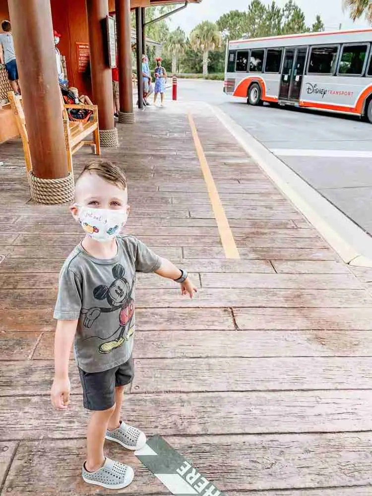 Little boy waiting for Disney World Bus as parks reopen