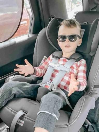 Toddler boy wearing sunglasses in car seat