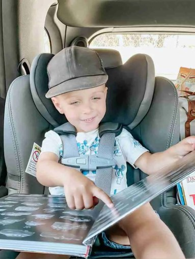 Toddler boy pointing at book on a road trip
