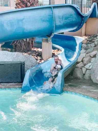 Father and son going down water slide at Palm Springs hotel
