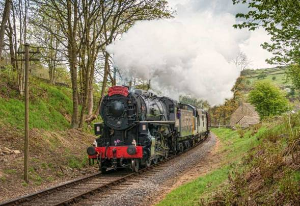 5820 & 37 075 approach Oxenhope carrying an appropriate VE Day headboard