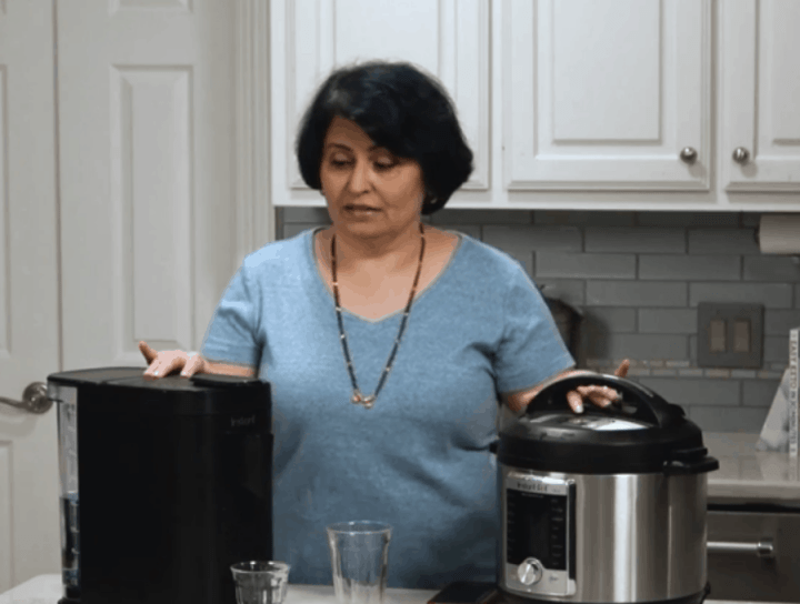 Picture of Urvashi Pitre comparing the size of the Instant Pod to a 6 quart Instant Pot.