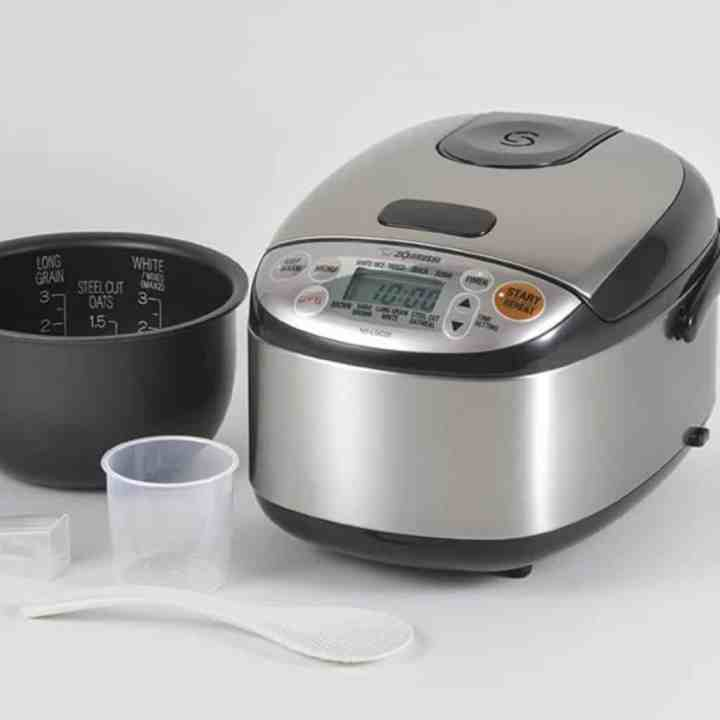 zojirushi rice cooker with accessories on a table in front of it