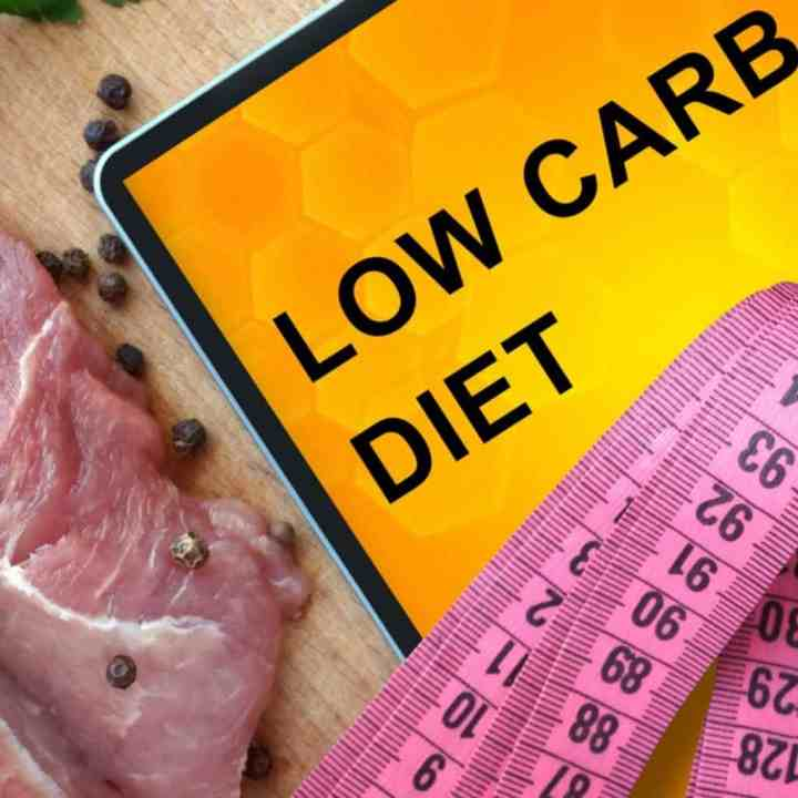yellow card reading low carb diet on a cutting board next to a cut of meat and a tape measure