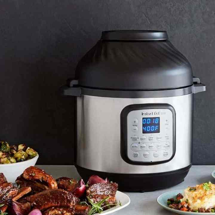 instant pot duo crisp on a counter surrounded by plates of food