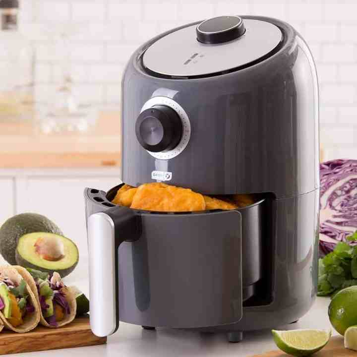 Dash compact air fryer with the basket open and tacos on the counter next to it