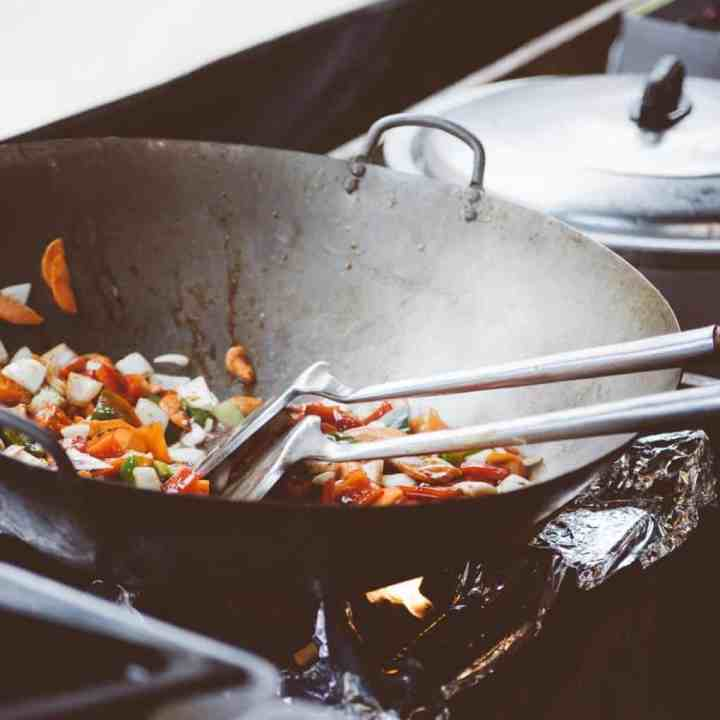 Image of a wok cooking food with two spatulas inside