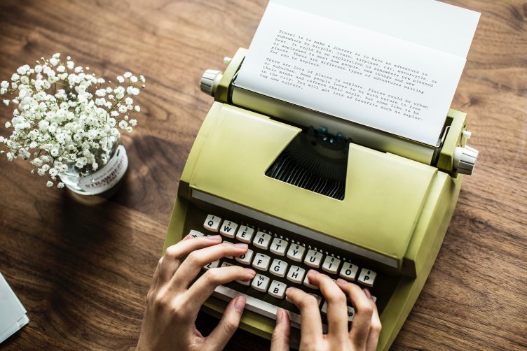 Someone typing on a pale green typewriter