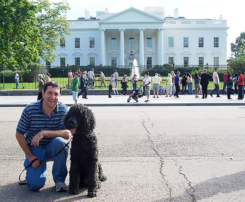 man with dog in front of White House