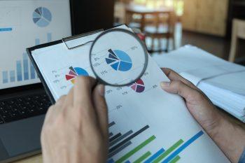 foto-de-pessoa-com-lupa-na-mao-olhando-relatorio-para-ressaltar-a-importancia-da-avaliacao-de-empresas