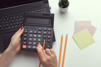 foto-de-mulher-calculando-em-sua-calculadora-com-lapis-papeis-e-computador-o-metodo-dos-multiplos