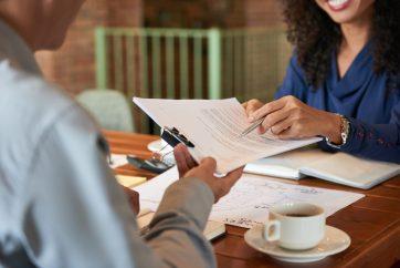 foto-de-dono-de-uma-empresa-diante-de-corretora-para-contrata-la-para-ilustrar-os-custos-para-vender-uma-empresa