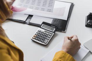foto-de-pessoa-diante-de-calculadora-e-relatorios-com-caneta-na-mao-para-calcular-o-ebitda