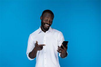 foto-de-homem-em-fundo-azul-olhando-feliz-para-seu-celular-demonstrando-que-encontrou-um-bom-negocio