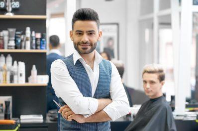 foto-de-cabeleireiro-com-cliente-ao-fundo-para-representar-o-mercado-de-saloes-de-beleza