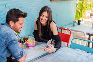 foto-de-casal-em-restaurante-olhando-no-celular-uma-plataforma-confiavel-para-vender-o-restaurante