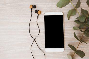 foto-de-fone-de-ouvido-e-celular-em-cima-da-mesa-para-ilustrar-artigo-sobre-podcasts-que-todo-empreendedor-deve-ouvir