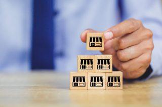 foto-de-pessoa-empilhando-caixinhas-com-ilustracao-de-empresas-que-representam-franquias