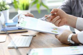 foto-de-pessoa-analisando-relatorio-em-prancheta-ao-avaliar-uma-empresa