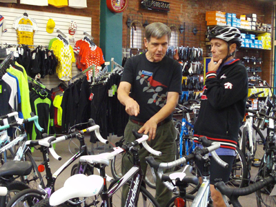 John Crandall, owner of the Old Town Bike Shop in Colorado Springs, advises customer Gayle Allen. Crandall found taking the tax credit for health insurance for his employees easy, but he's in the minority among other business owners across Colorado.  Credit: Ann Imse/Colorado Public News