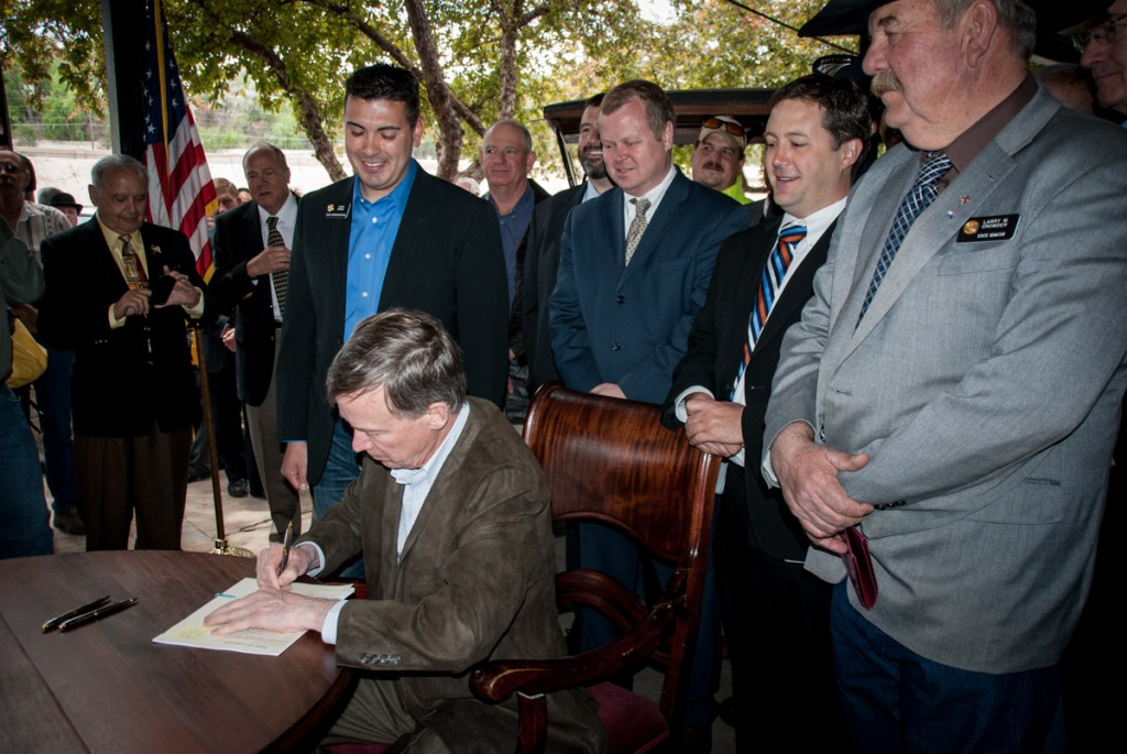 Governor John Hickenlooper signs a bill that creates a commission aimed at preserving and expanding Amtrak's Southwest Chief passenger rail service in Southern Colorado. Standing behind him are State Rep. Leroy Garcia (D-Pueblo), Amtrak's Ray Lang, Pueblo County Commissioner Sal Pace and State Senator Larry Crowder (R-Alamosa).