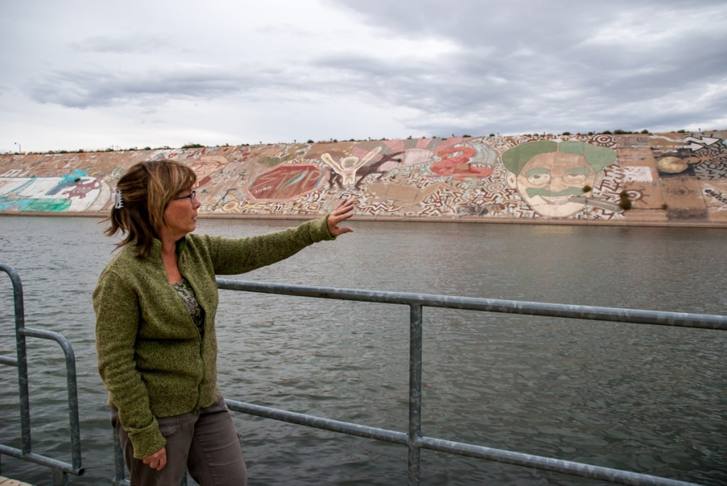 Cynthia Ramu, volunteer coordinator for the Pueblo Levee Mural Project, points to various elements of the mural. Ramu has worked on dozens of the mural pieces.