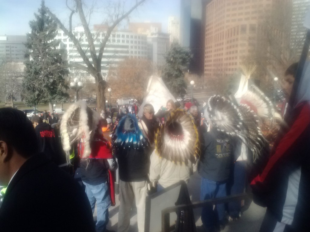 Tribal leaders and others gather outside the state capitol to commemorate the 150th anniversary of the Sand Creek Massacre.