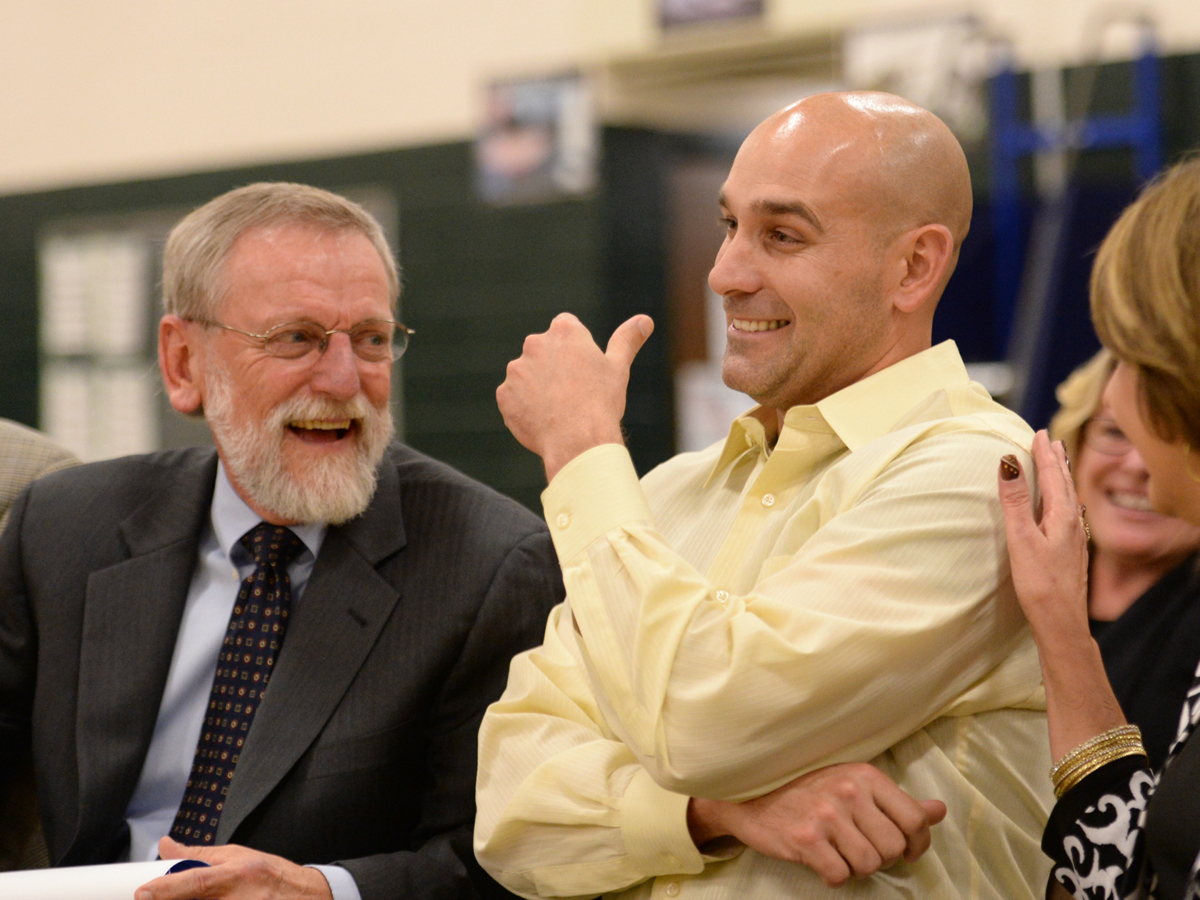 Science teacher Ryan Moore receives congratulations from Colorado Interim Commissioner of Education Dr. Elliott Asp, left, as Moore accepts the Colorado 2015-16 Milken Educator Award.