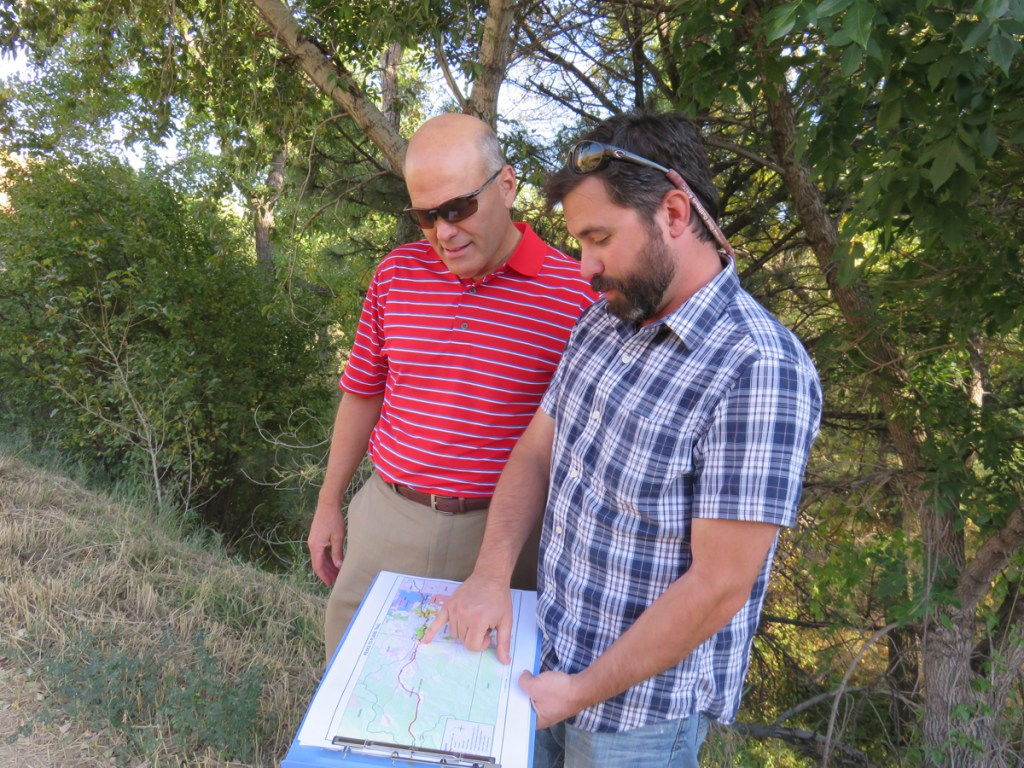 Tom Hoby, Director of Open Space and Parks for Jefferson County, looks on as Scot Grossman, a research coordinator and planner, shows the gaps in the Clear Creek Trail west of Denver.
