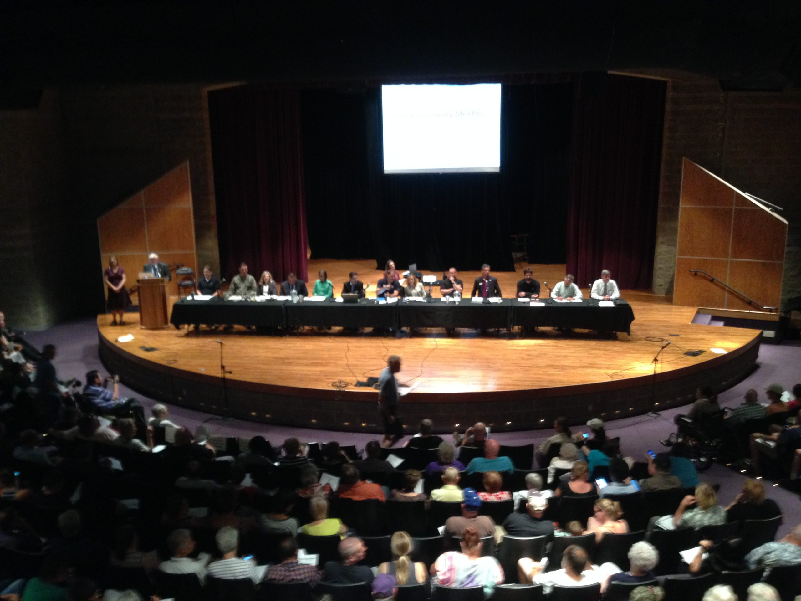 Panelists speak to a packed auditorium at Thursday's community meeting at Mesa Ridge High School