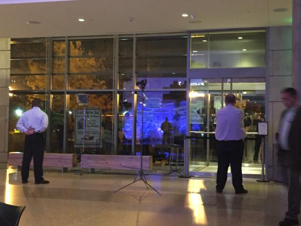Guards at History Colorado watch doors as Green Party activists pound them in protest of a U.S. Senate debate in Denver that excluded their candidate