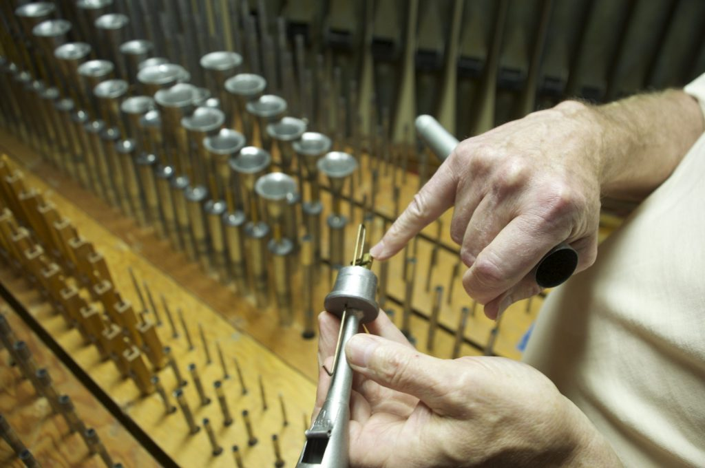 Dave Weesner holds a small tuned pipe in the organ pipe chamber.