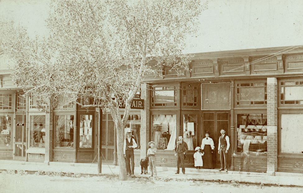 Moritz Bernstein, third from left, dressed in a suit, stands with hands in pockets. Customers near him stand in front of Bernstein's Dry Goods Store in Walsenburg, Colorado. (Circa 1890).