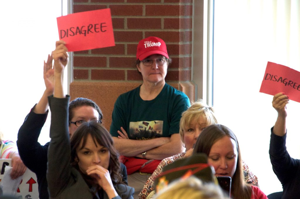 """A woman in a """"Team Trump"""" hat looks on as protestors hold """"disagree"""" signs in response to a comment made by Rep. Lamborn."""