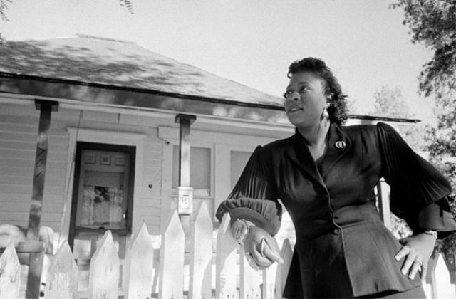 Fannie Mae Duncan leaning on a white picket fence outside her home in Colorado Springs, 1955.