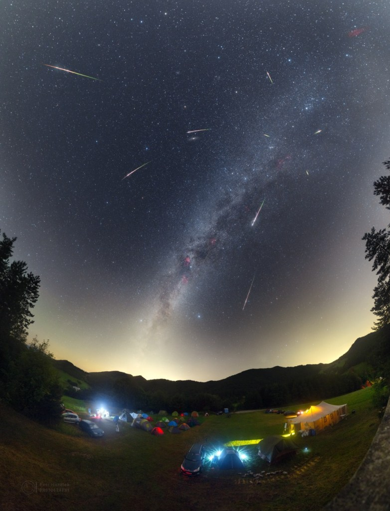 This weekend is the peak of the annual Perseid Meteor Shower. Normally bright and colorful, the Perseid shower meteors are produced by dust swept up by planet Earth from the orbit of Comet Swift-Tuttle. In this composite image Perseid meteors from the 2016 meteor shower are set against a starry background along the Milky Way, with even the faint Andromeda Galaxy just above center. In the foreground, astronomers of all ages have gathered on a hill above the Slovakian village of Vrchtepla.