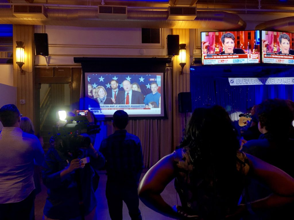 Stephany Rose Spaulding, who lost her congressional bid to incumbent Republican Doug Lamborn, watches as Governor-elect Jared Polis makes his acceptance speech.