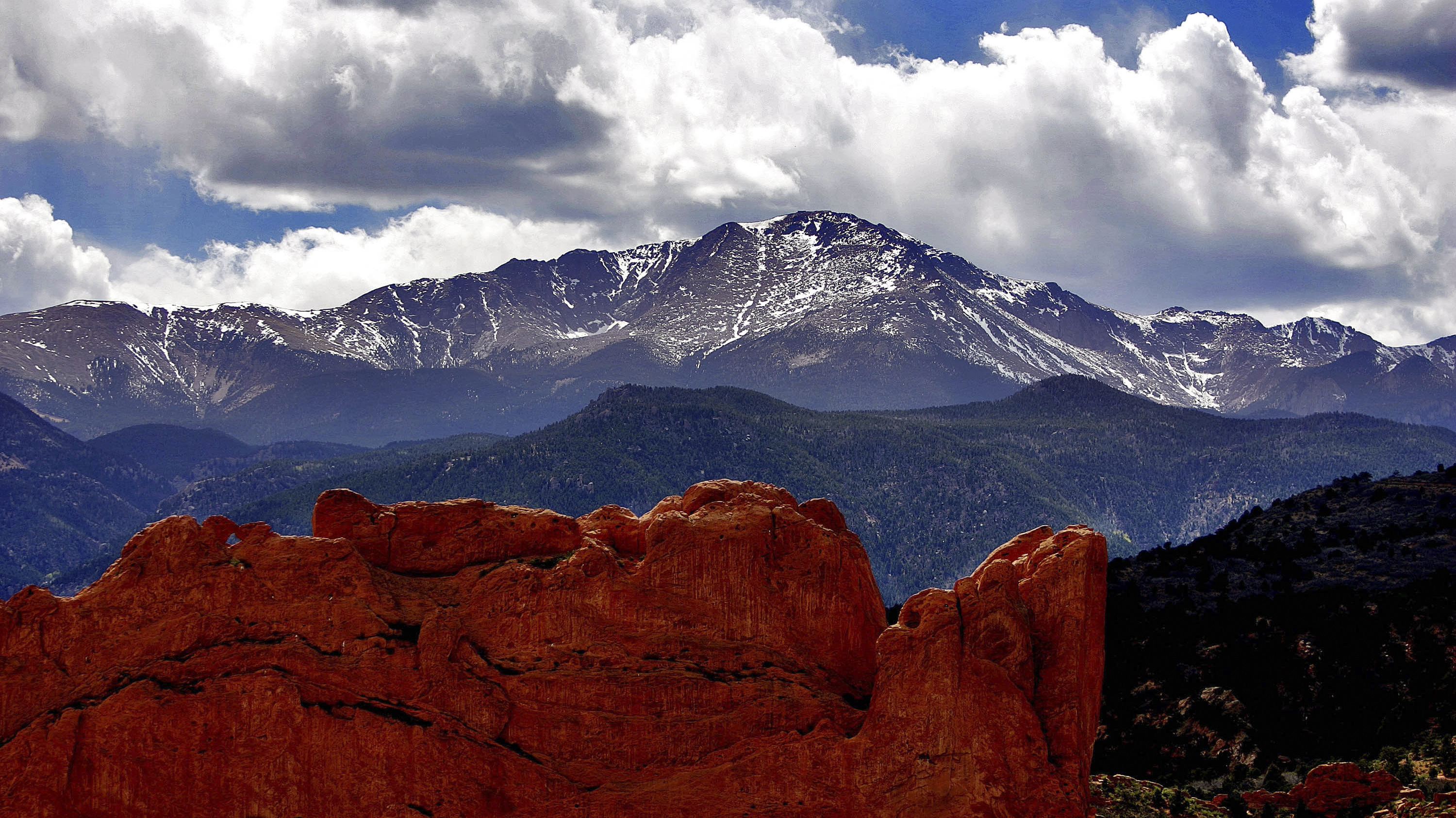 <p>The sun breaks through the clouds to highlight the summit of Pikes Peak as seen from the Garden of the Gods in Colorado Springs, Colo.</p>