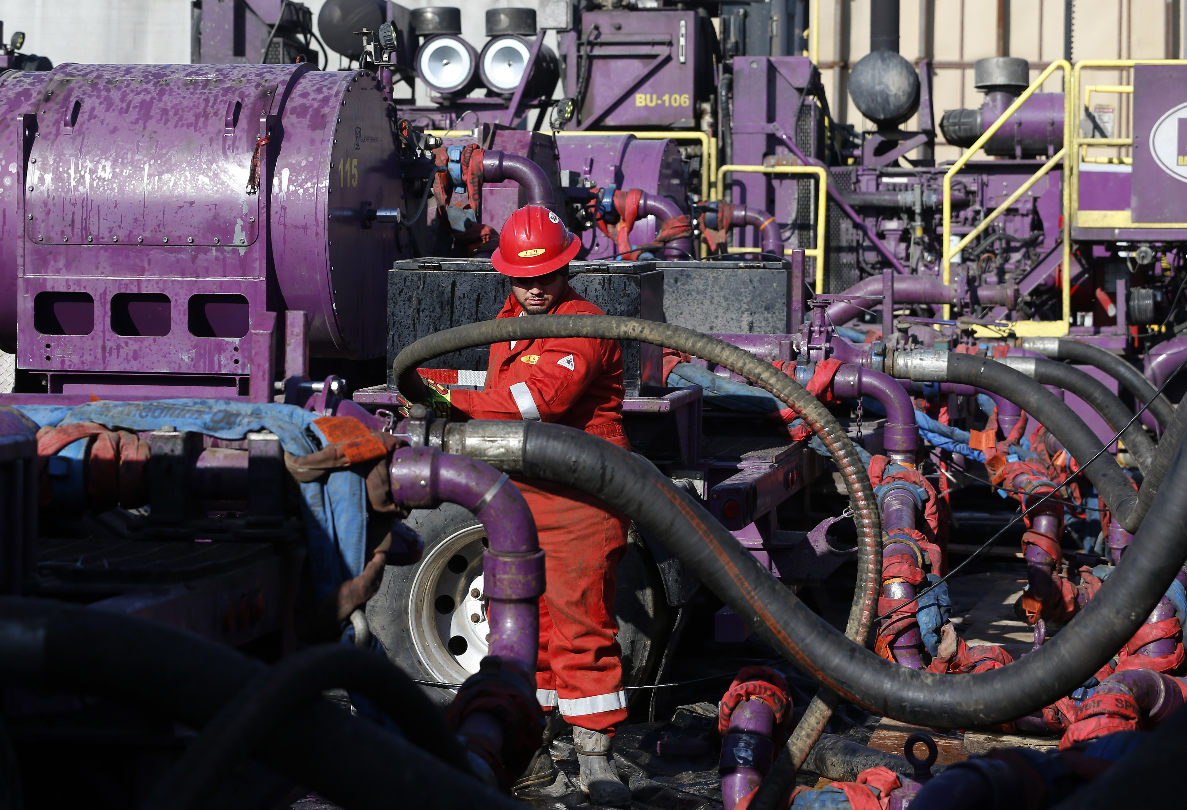 <p>In this March 25, 2014 photo, a worker adjusts hoses during a hydraulic fracturing operation at an Encana Corp. oil well in Weld County, near Boulder County.</p>