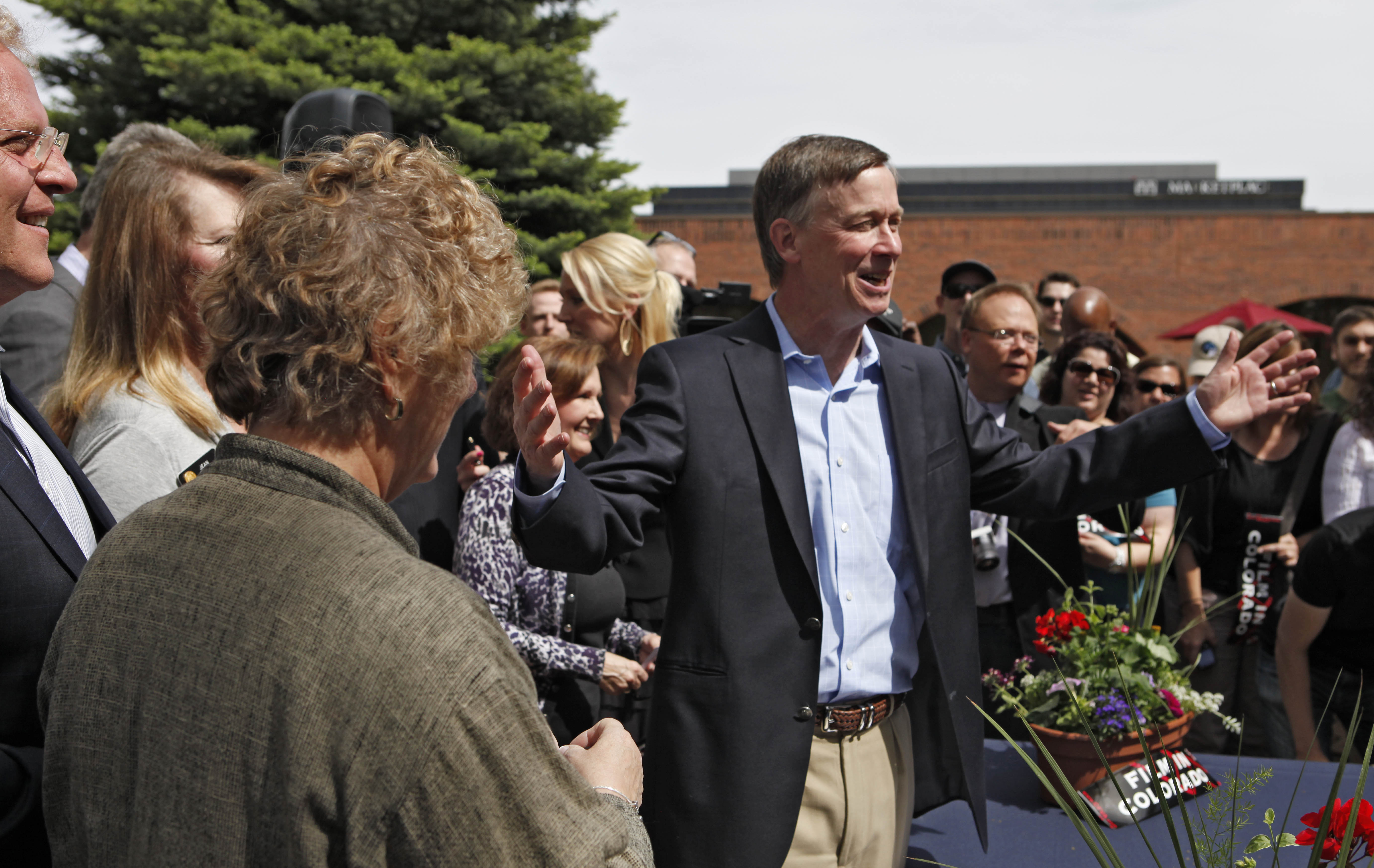 <p>Colorado Gov. John Hickenlooper passes out pens to members of the Legislature at a ceremony in Denver on Friday, May 18. 2012, after he signed a measure into law to increase tax rebates and incentives for film production in Colorado.</p>