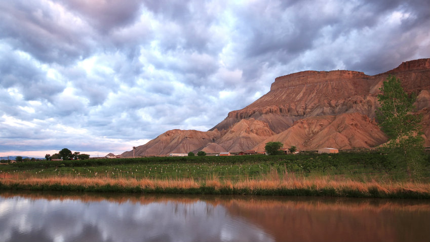 <p>Mount Garfield reflects in the irrigation canal in Palisade, Colorado.</p>