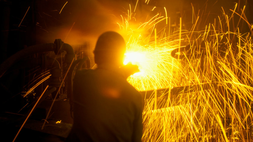 <p>Worker opening tap hole in modern-day furnace as sparks fly.</p>