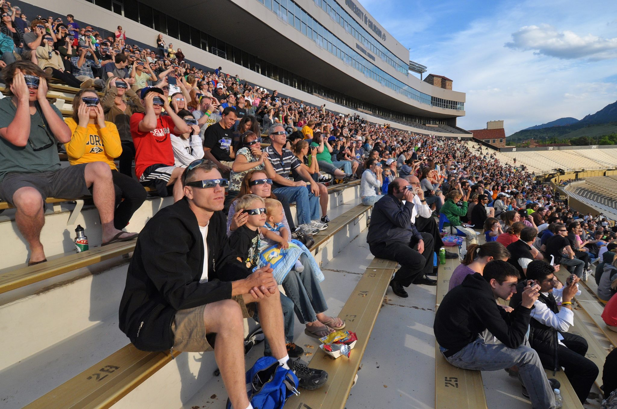 <p>Thousands of people wearing special eclipse glasses watched a partial solar eclipse at CU's Folsom Field in 2012.</p>