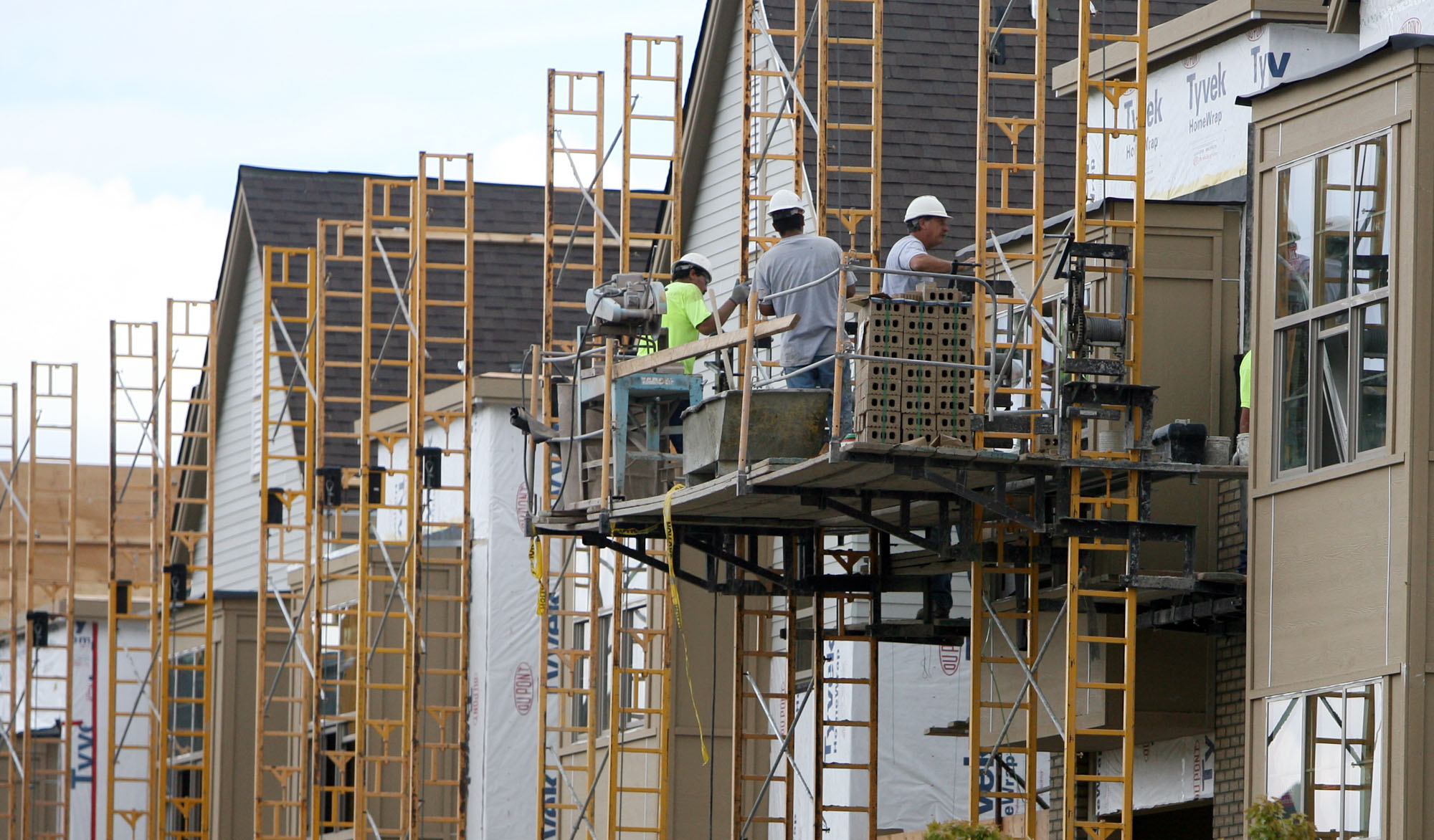 Workers completingthe facades on a row of condominiums in the Denver area.