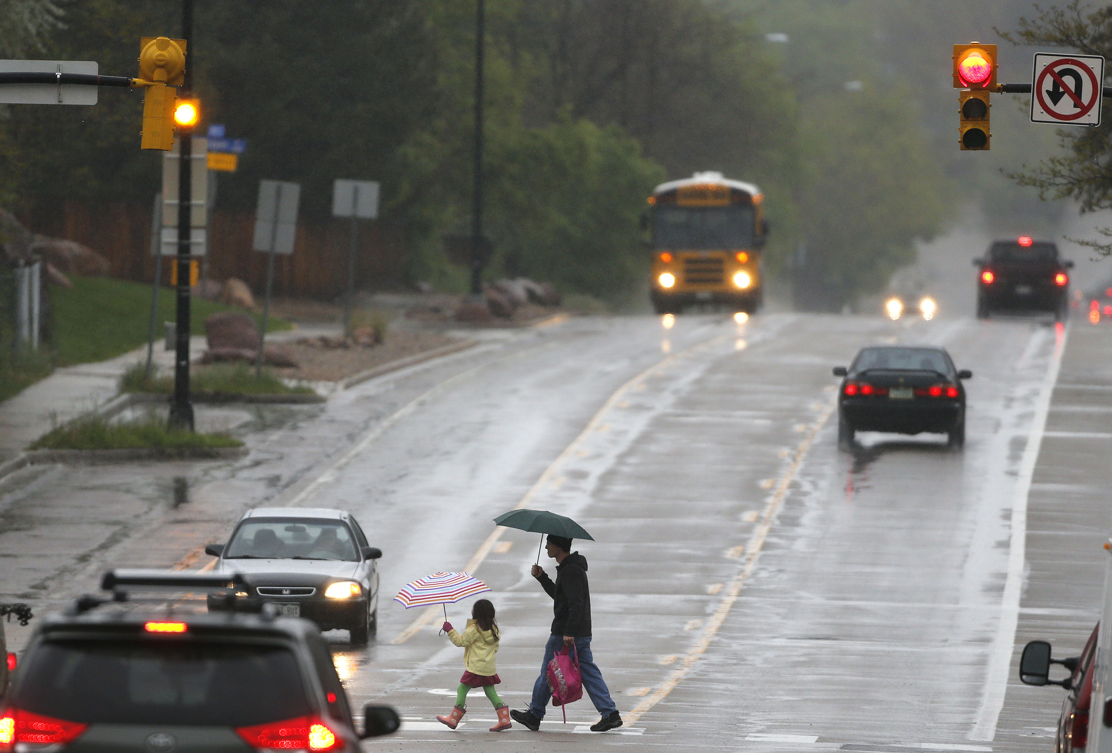 <p>A man walks a student to school in the rain, in Boulder, Colo., Tuesday, May 19, 2015. Colorado braced for a spring storm with unseasonably heavy rains and several inches of snow expected in the high country.</p>