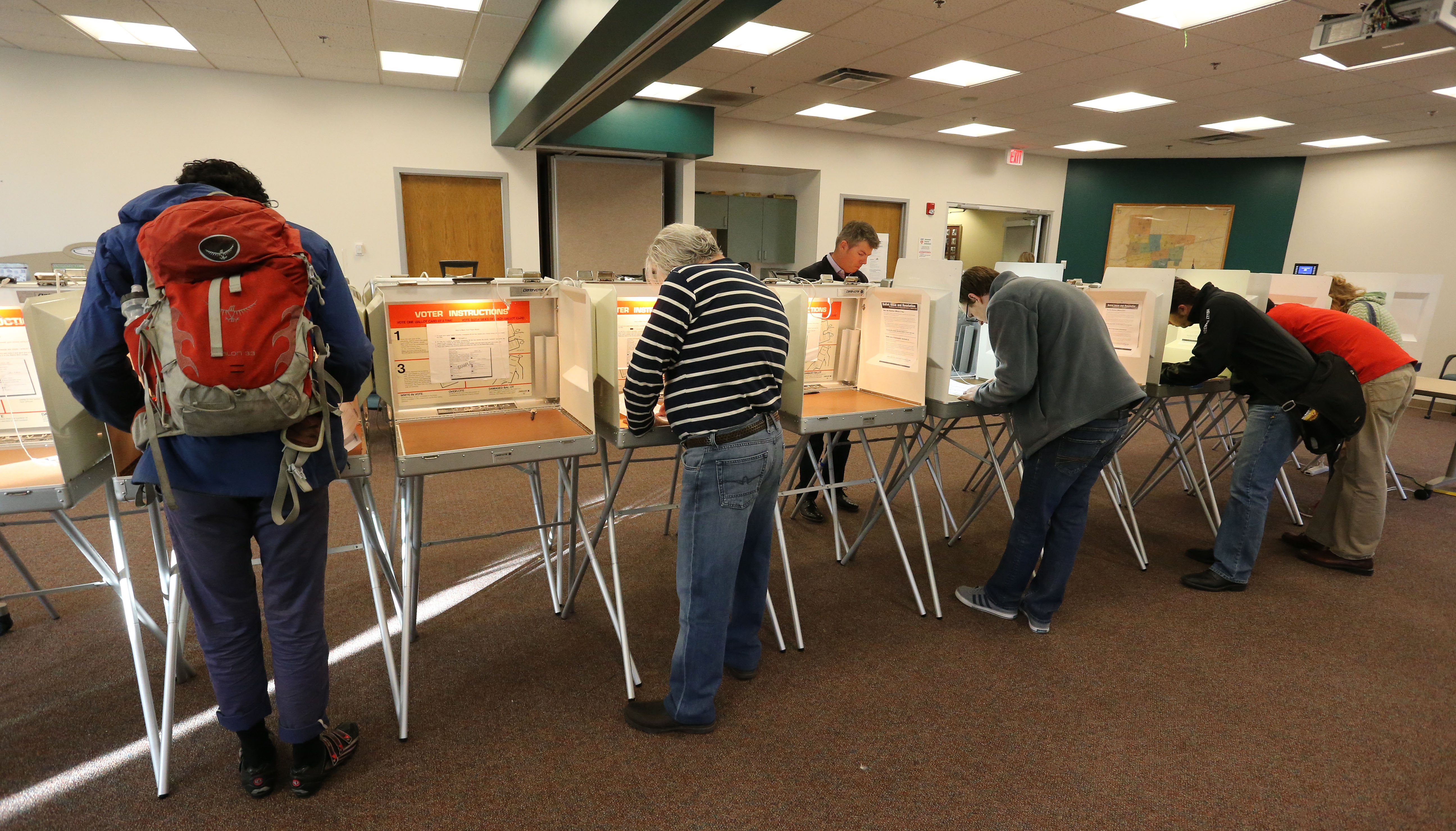 <p>Voters complete their ballots inside a polling center at the Boulder County Clerk and Recorder's officeon Election Day2014.</p>